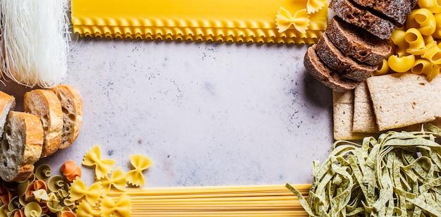 Verschillende pasta achtergrond. brood en verschillende pasta op grijs-blauwe achtergrond, kopie ruimte, bovenaanzicht.