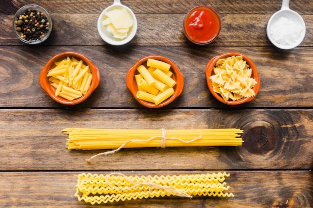 Verschillende pasta in de buurt van sauzen en specerijen