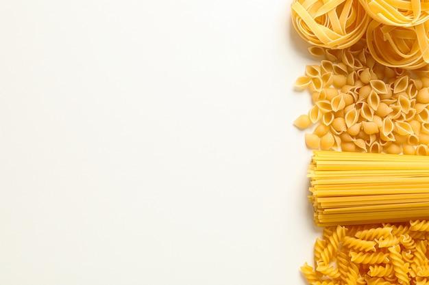 Verschillende pasta op witte achtergrond, ruimte voor tekst. droog ongekookte hele pasta
