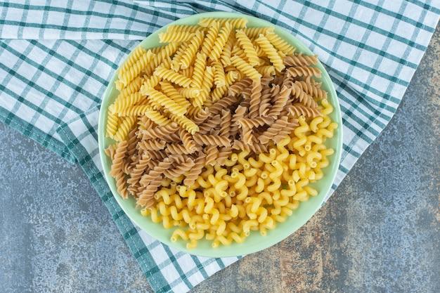 Verschillende pasta's in kom op de handdoek, op het marmeren oppervlak.