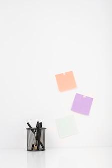 Verschillende pennen in houder dichtbij kleurrijke zelfklevende nota's die op muur worden geplakt