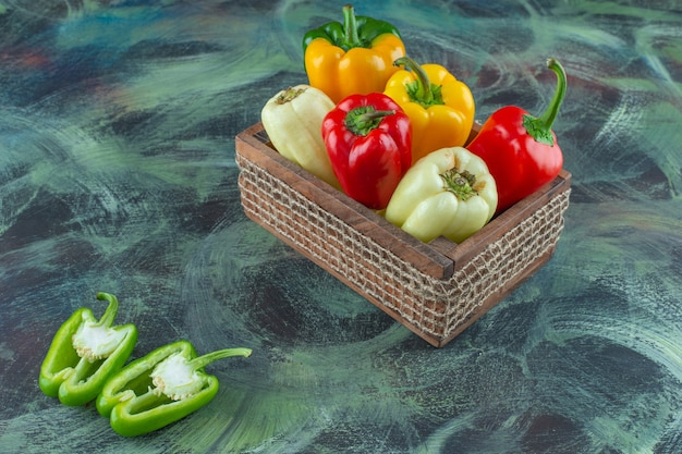 Verschillende peper in een houten kist op het marmeren oppervlak