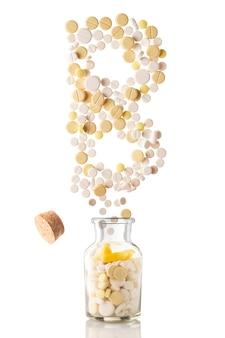Verschillende pillen vliegen uit een glazen pot in de vorm van letter b, geïsoleerd op een witte achtergrond