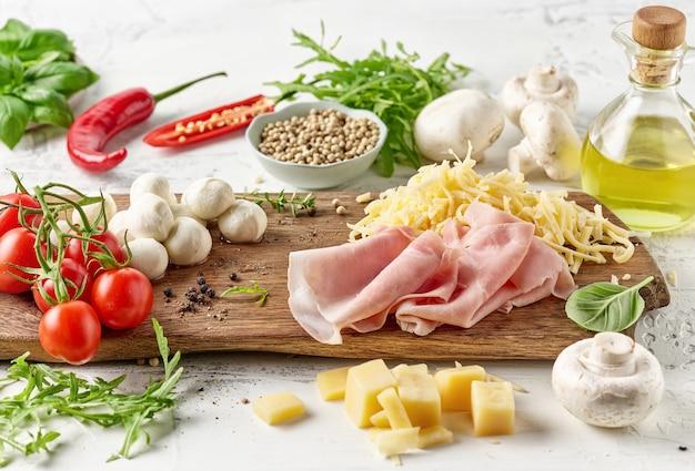 Verschillende pizza-ingrediënten op rustieke houten snijplank