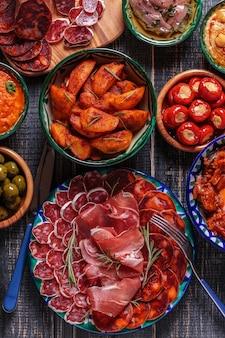 Verschillende plakjes jamon, chorizo, salami, kommen met olijven, paprika, ansjovis, pittige aardappelen, gepureerde kikkererwten op een houten tafel.