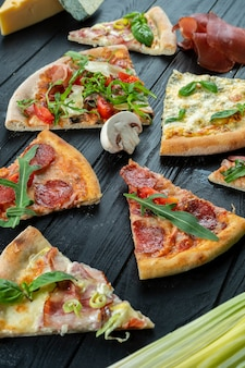 Verschillende plakjes pizza op donkere houten achtergrond. italiaanse keuken. eten foto achtergrond.
