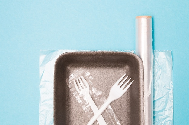Verschillende plastic wegwerpverpakkingen op een blauwe achtergrond, een voedselbakje, een rol plastic tape en een zak voor het invriezen van voedsel, een wegwerpvork en een drinkbuis, milieuvervuilingsconcept
