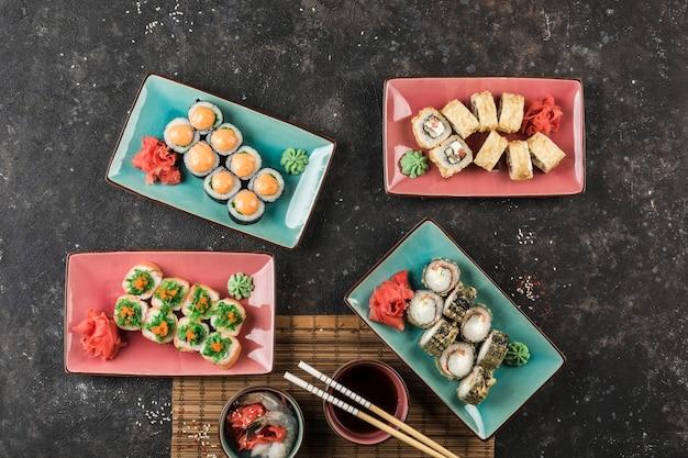 Verschillende platen met sushibroodjes die door de chef-kok op een donkere achtergrond worden gediend. uitzicht van bovenaf met een kopie-ruimte. restaurant eten. plat leggen