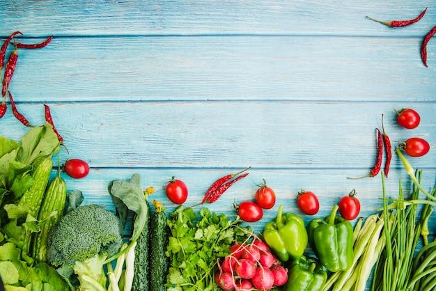 Verschillende rauwe groente op blauwe houten tafel