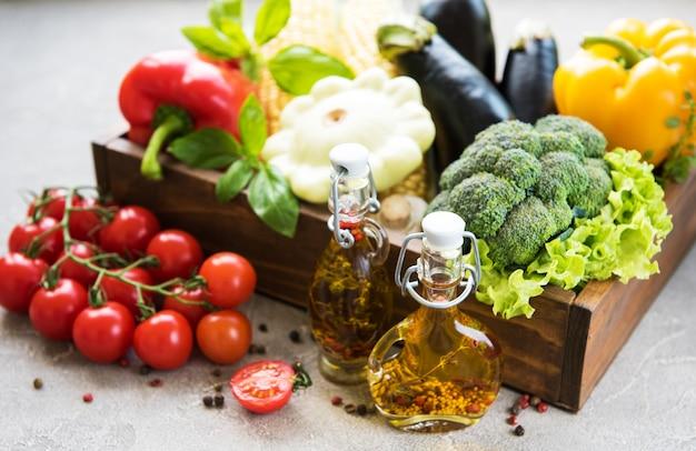 Verschillende rauwe groenten en olijfolie op een concrete achtergrond