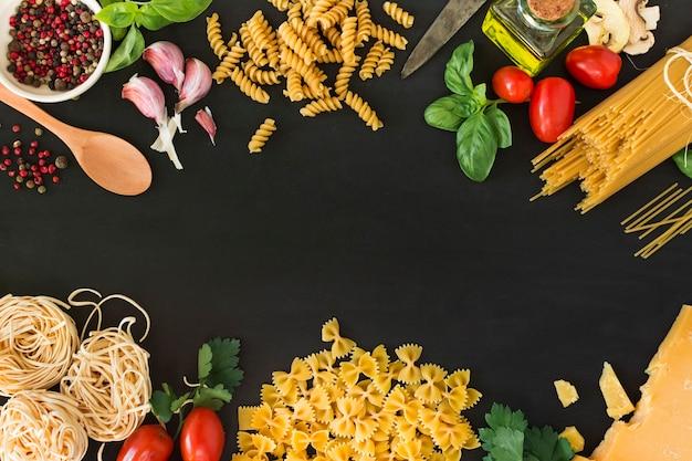 Verschillende rauwe pasta met ingrediënten op zwarte achtergrond