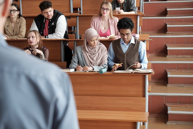 Verschillende rijen hedendaagse interculturele universiteitsstudenten zitten aan lange houten bureaus in de collegezaal en luisteren naar de professor tijdens de les