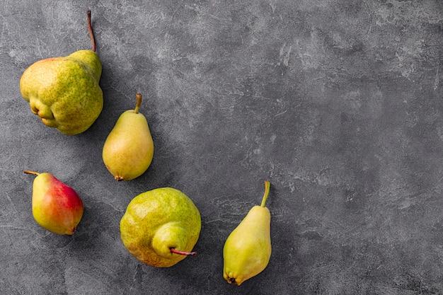 Verschillende rijpe peren op grijze achtergrond bovenaanzicht, trending lelijke vruchten. hoge kwaliteit foto
