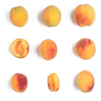 Verschillende rijpe perziken op een witte achtergrond. twee worden gesneden. uitzicht van boven.