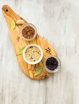 Verschillende rijstsoorten in kleine kommen op een houten bord