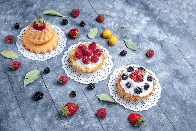 Verschillende romige taarten met bessen en vers fruit op een helder, bessen-koekje met vers fruit