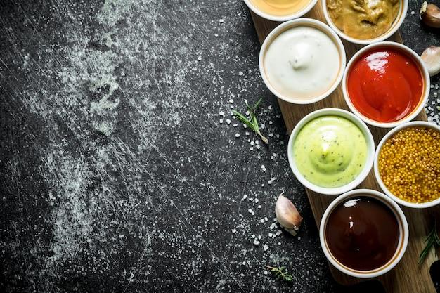Verschillende sauzen in de kommen op de snijplank. op donkere rustieke tafel