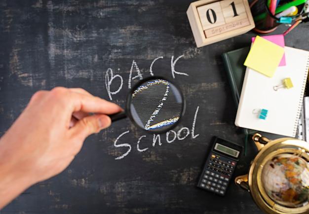 Verschillende schoolbenodigdheden op donkere achtergrond. concept terug naar school