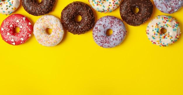 Verschillende smakelijke donuts op gele achtergrond, bovenaanzicht