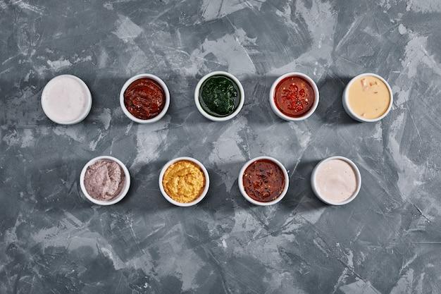 Verschillende smakelijke sauzen in kommen, verschillende sauzen op grijze stenen achtergrond, bovenaanzicht.