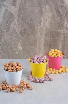 Verschillende smaken en kleuren popcornsuikergoed gesorteerd in kleurrijke emmers op marmer.