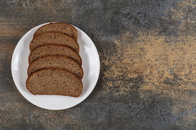 Verschillende sneetjes roggebrood op een witte plaat