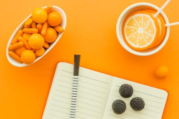 Verschillende snoepjes en lollies met blocnote en pen op oranje achtergrond