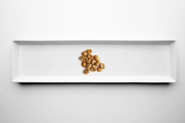 Verschillende soorten artisanale professionele roosterende koffie geïsoleerd op een witte plaat, bovenaanzicht