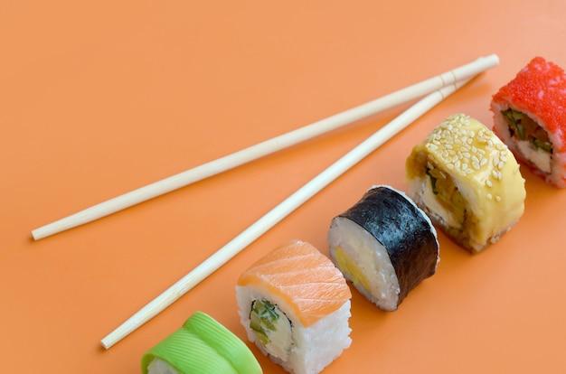 Verschillende soorten aziatische sushi rolt op oranje achtergrond. minimalisme bovenaanzicht plat lag met japans eten
