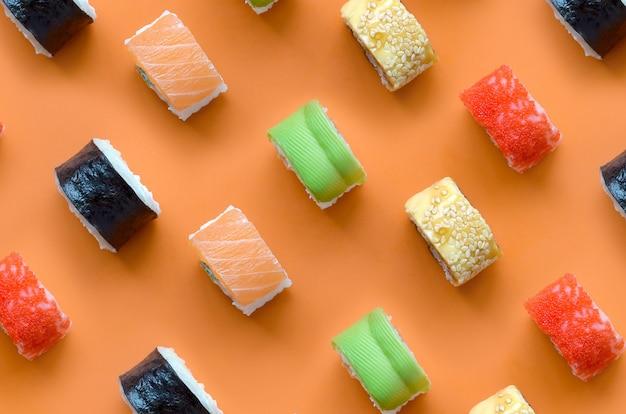 Verschillende soorten aziatische sushi rolt op oranje achtergrond. minimalisme bovenaanzicht plat lag patroon met japans eten