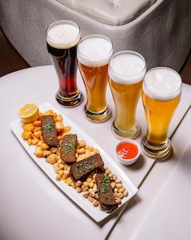 Verschillende soorten bier met crackers dushbara kaas pistachenoten
