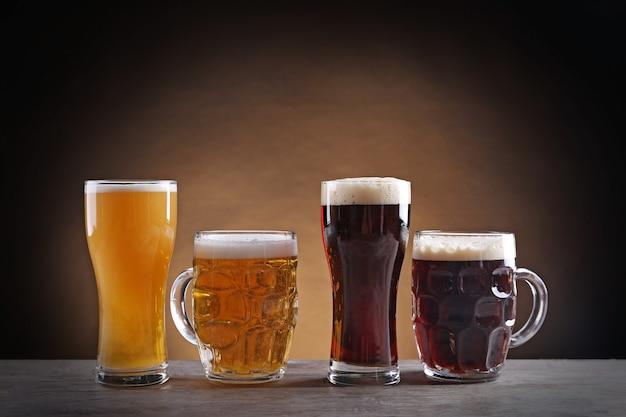 Verschillende soorten bier van de tap in glazen op houten tafel