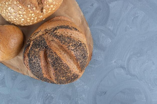 Verschillende soorten brood gebundeld op een houten bord op marmeren tafel.