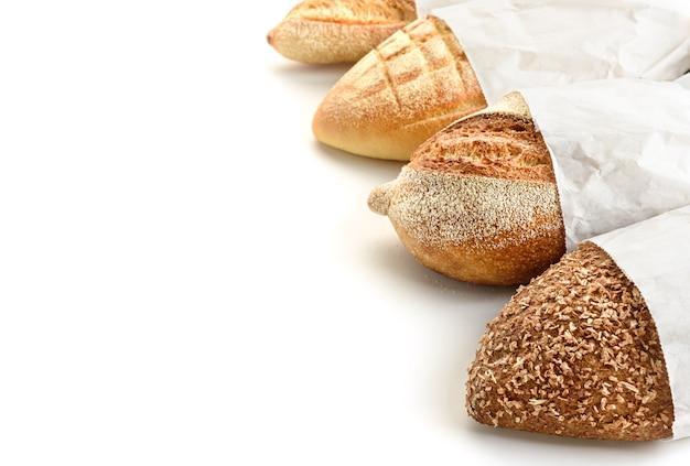 Verschillende soorten brood in papieren zakken op een witte achtergrond.