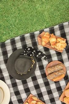 Verschillende soorten brood met hoed op deken over het groene gras