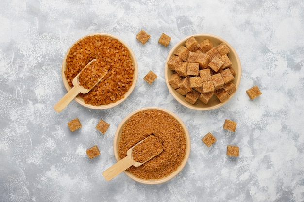 Verschillende soorten bruine suiker op concrete, bovenaanzicht