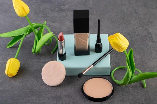 Verschillende soorten cosmetica op grijze ondergrond.
