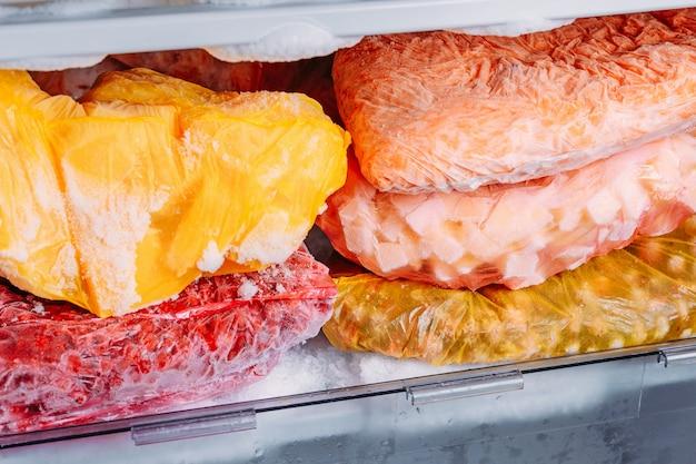 Verschillende soorten diepgevroren groenten in plastic zakken in een koelkast