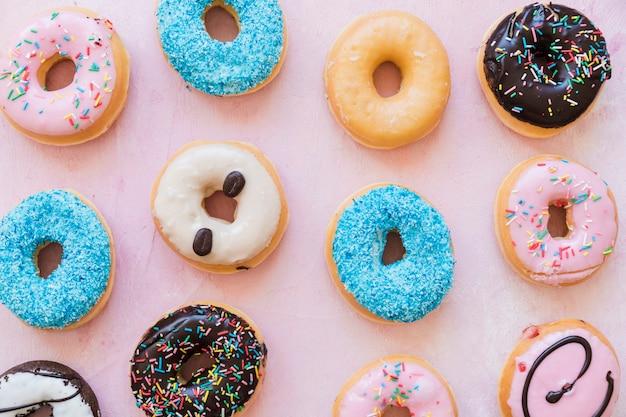Verschillende soorten donuts op een rij op roze achtergrond
