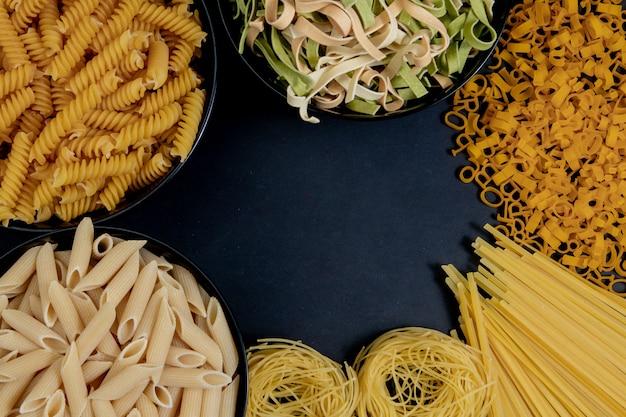 Verschillende soorten droge pasta op de plaat en in kommen op zwarte achtergrond. ruimte voor tekst, bovenaanzicht