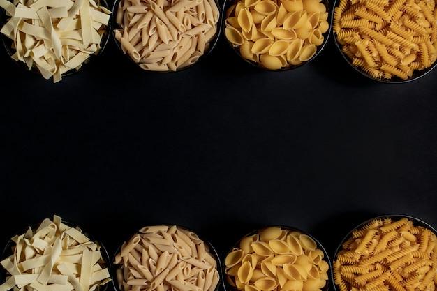 Verschillende soorten droge pasta op de plaat en in kommen op zwarte achtergrond.