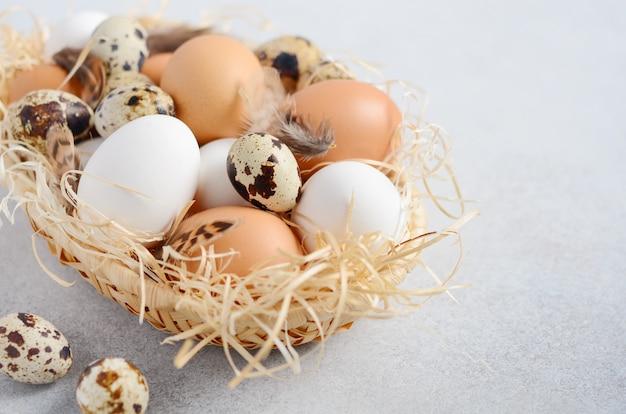 Verschillende soorten eieren in een mand op een grijze betonnen tafel
