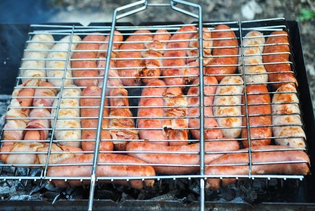 Verschillende soorten en kleuren worstjes met vlees worden gebakken op een vuur in het bos