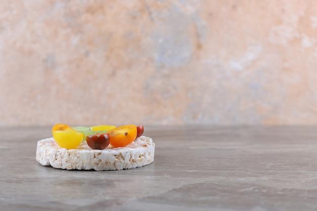 Verschillende soorten fruit op de gepofte rijstwafels, op het marmeren oppervlak
