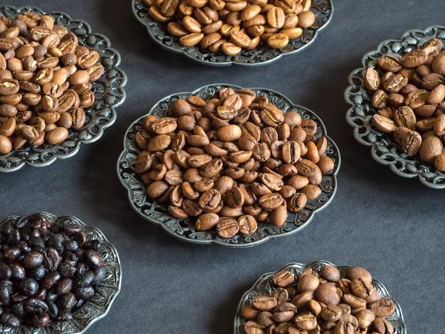 Verschillende soorten geroosterde koffiebonen op een zwarte achtergrond.