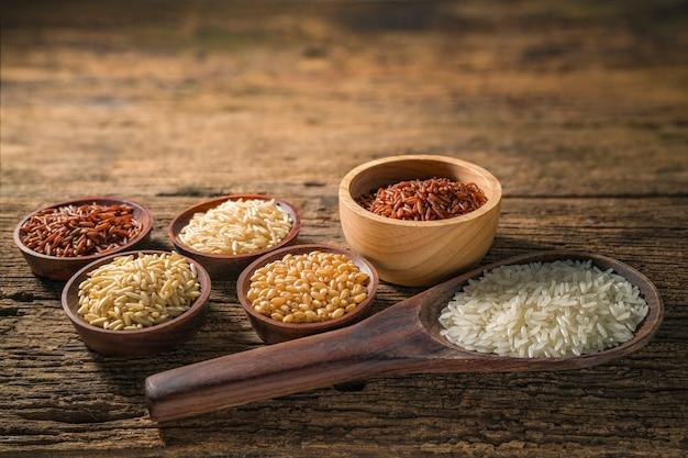 Verschillende soorten graankorrels (tarwe, rijst, bruine rijst, boekweit, gerst, zwarte sesam, gierst, lotuszaden, job's tranen). diverse rauwe ongekookte granen op hout achtergrond.