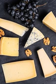 Verschillende soorten heerlijke kaas met walnoten en druiven. zwarte achtergrond. bovenaanzicht