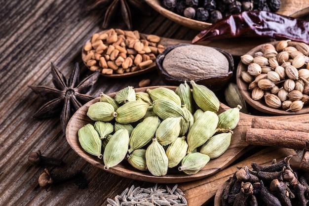 Verschillende soorten hele indiase kruiden in houten achtergrond.