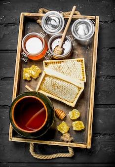 Verschillende soorten honing op houten dienblad. op een zwarte rustieke tafel.