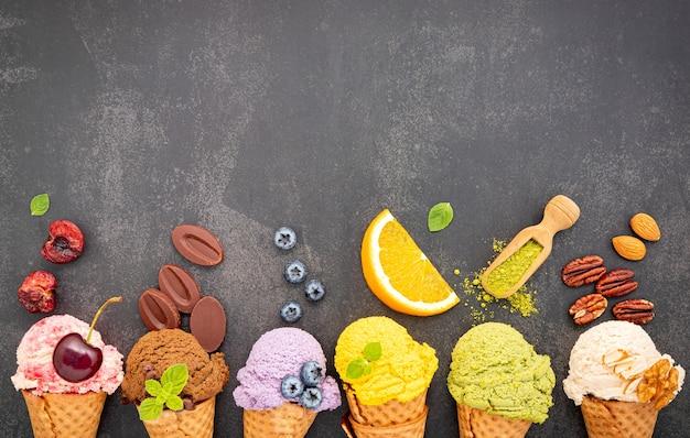 Verschillende soorten ijssmaak in kegels, bosbessen, groene thee, pistache, amandel, sinaasappel en kers op donkere steen